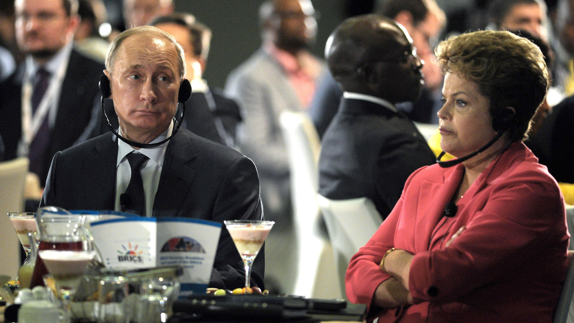Russian President Vladimir Putin, left, and Brazilian President Dilma Rousseff sit awkwardly at a table.