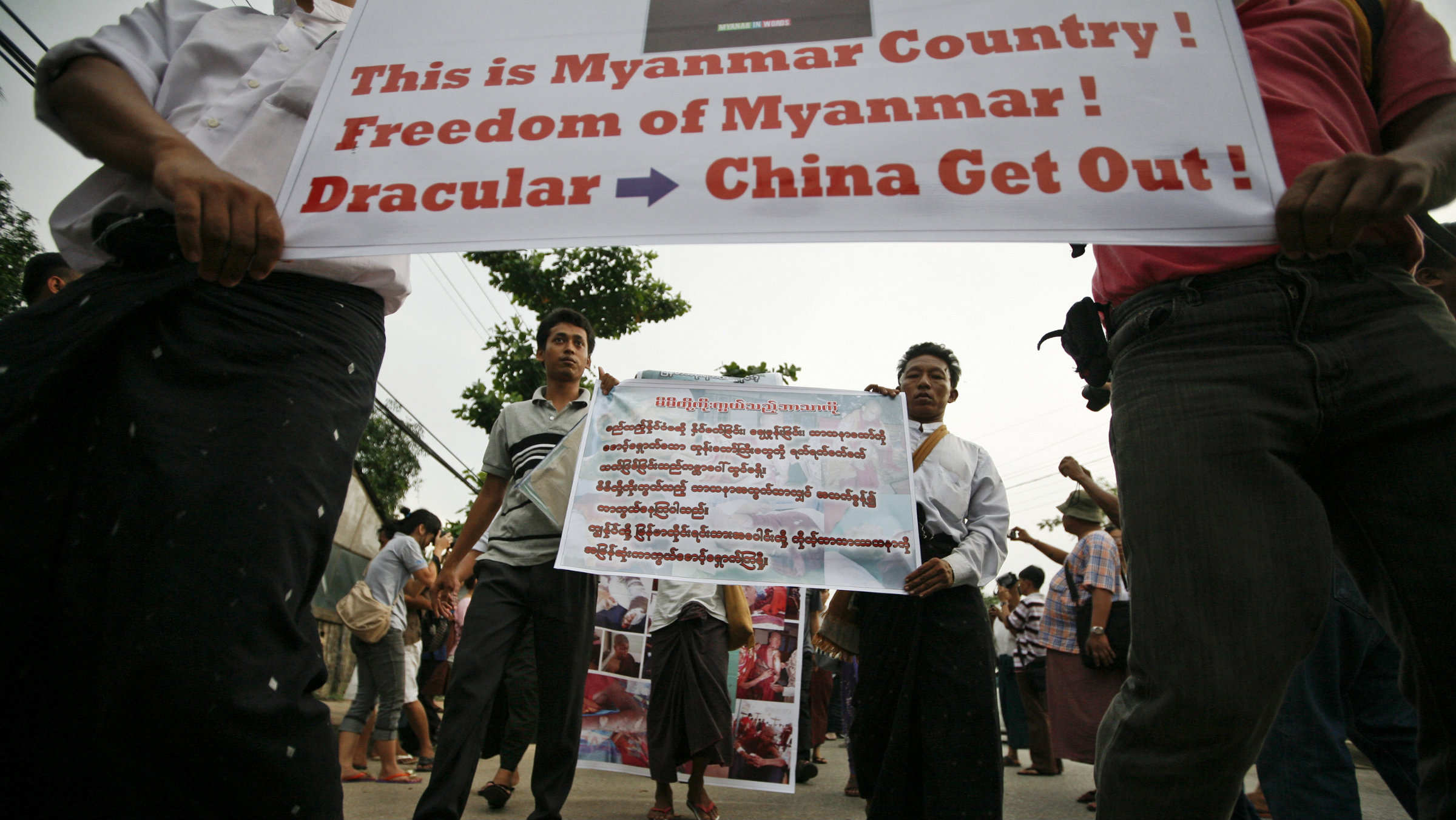 Protesters hold posters during a peaceful protest in support of Buddhist monks injured during a riot and against the Latbadaung Mountain Copper Mine project, in Yangon December 2, 2012.