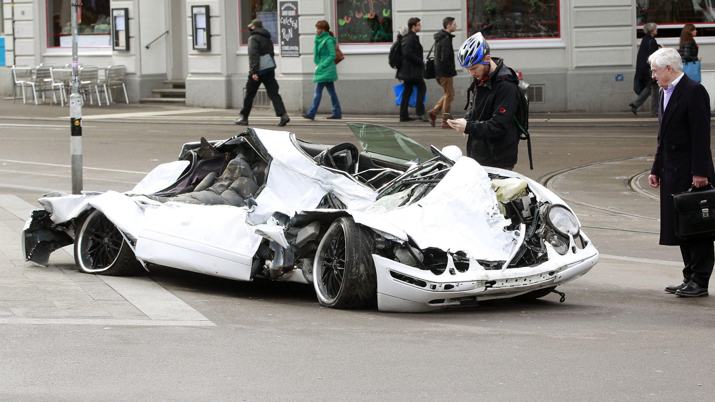 People stand beside a destroyed Mercedes car placed by Alliance24 car insurance company to promote a competition in front of a railway station in Zurich