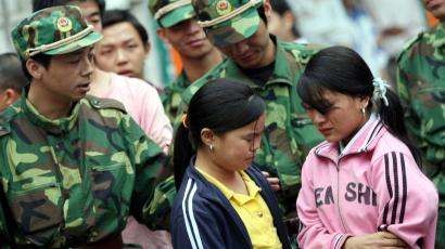Two girls are rescued from a factory in Dongguan, Guangdong province, April 28, 2008. More than 1,000 children, aged between 9 and 16 from poor families in Liangshan, Sichuan province, have been lured to Dongguan, Shenzhen and Huizhou in the Pearl River Delta area, to work as cheap labor in factories, Southern Metropolis Newspaper reported. Picture taken April 28, 2008.