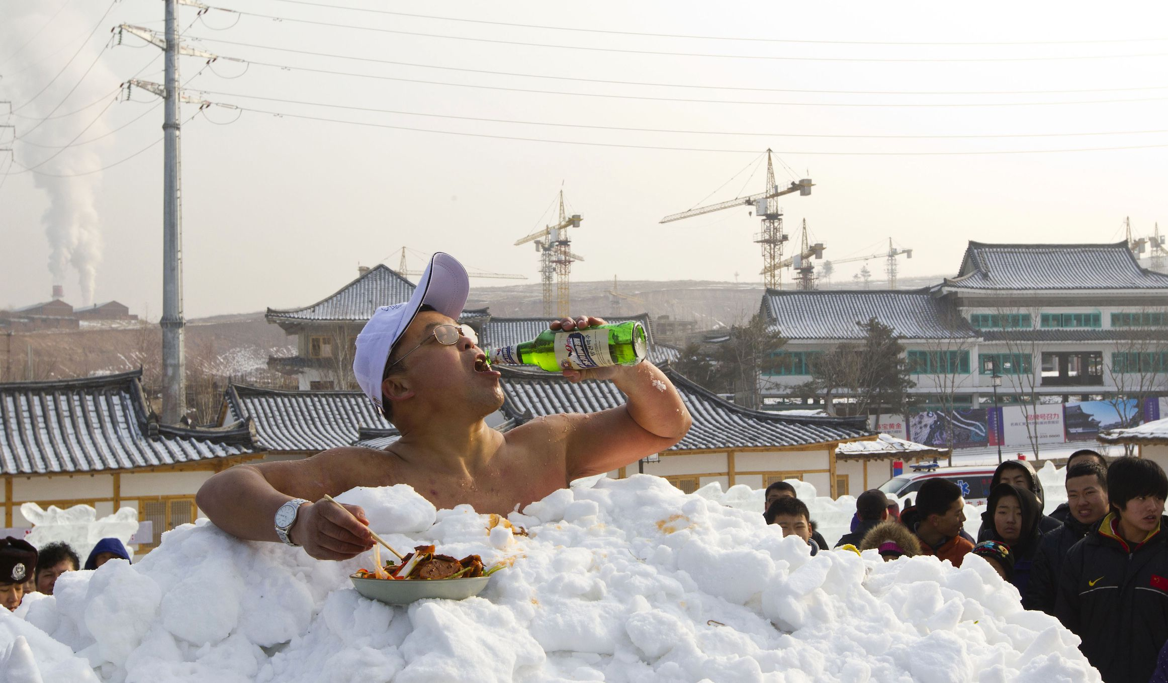 Jin Songhao drinks beer as he sits in snow during a cold endurance performance in Yanji, Jilin province, January 12, 2013. Jin set the Guinness record for the longest time spent in direct full body contact with snow on January 17, 2011 with a time of 46 minutes and seven seconds, local media reported. Picture taken January 12, 2013. REUTERS/Stringer (CHINA - Tags: SOCIETY ENVIRONMENT) CHINA OUT. NO COMMERCIAL OR EDITORIAL SALES IN CHINA - RTR3CGWW
