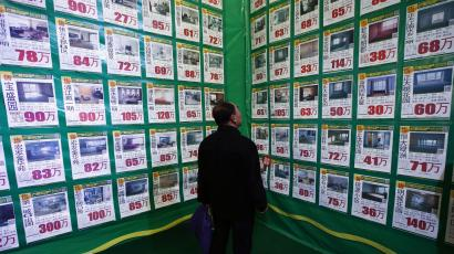 A man looks at posters on a giant advertising board showing information on second-hand apartments at a real estate exhibition in Shenyang, Liaoning province April 17, 2014. China's real estate investment rose 16.8 percent in first three months of 2014 from a year earlier, and revenues from property sales dropped an annual 5.2 percent, the National Bureau of Statistics said on Wednesday. REUTERS/Stringer china housing market home sales prices sales financial crisis gdp
