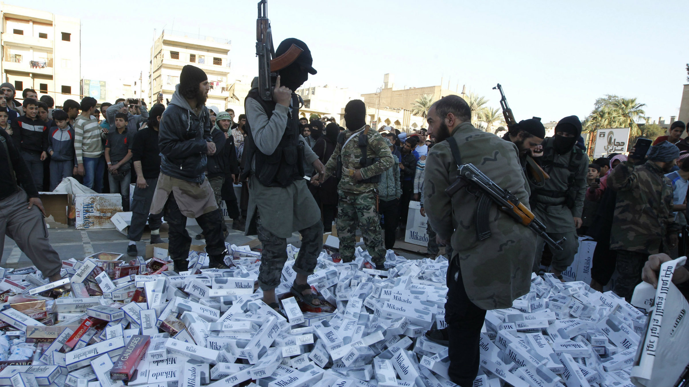 ISIL fighters stamp on confiscated cigarettes before setting them on fire in the city of Raqqa on April 2, 2014.