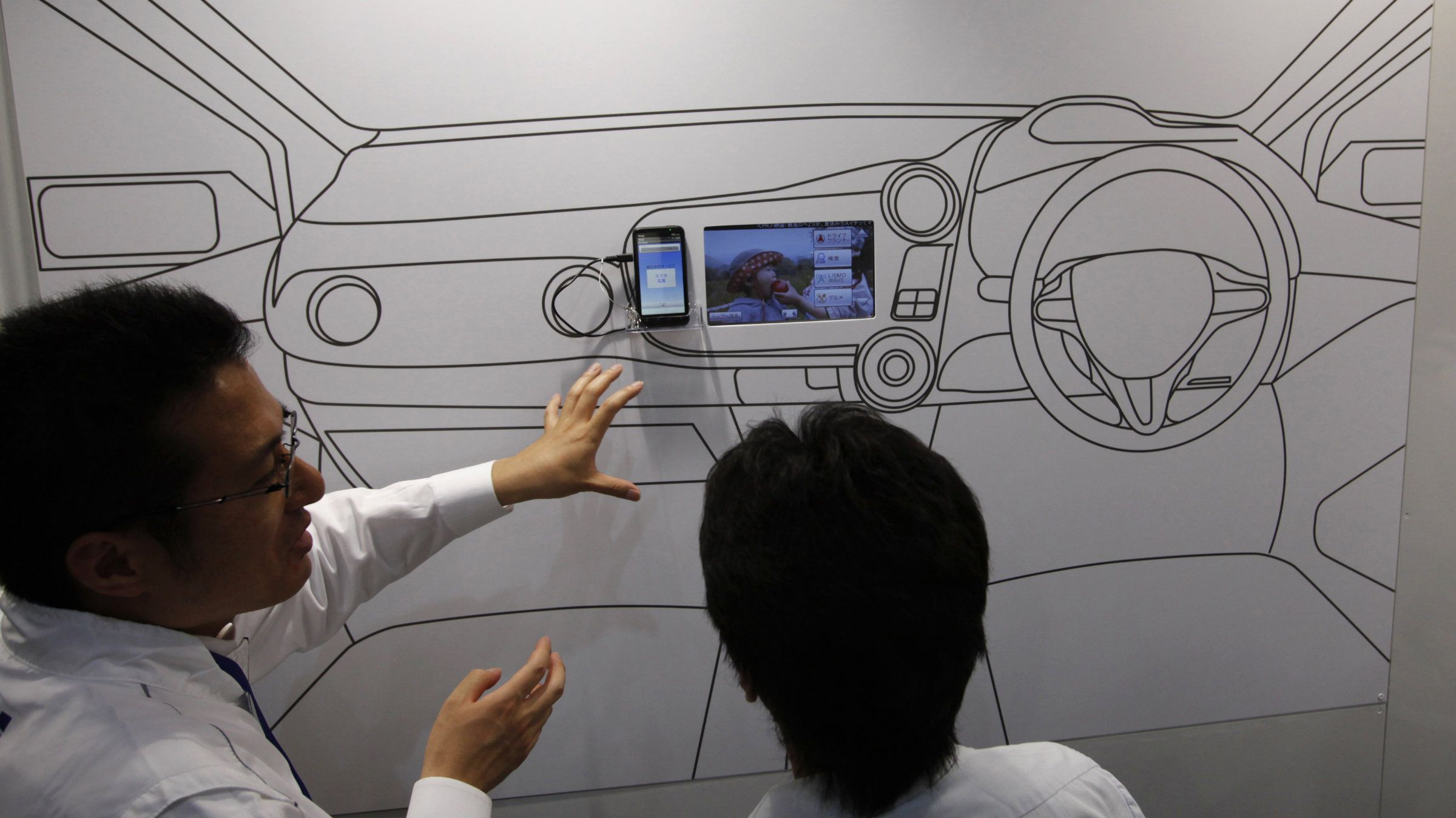 A smartphone and mobile phone carrier company demonstrates in-car smartphone device technology at Wireless Japan 2012, a smartphone and mobilephone technology exhibition, in Tokyo May 31, 2012. Japanese factory output rose in April at a slower pace than expected, in a discouraging sign that China's slowing economy and Europe's debt crisis will weigh on Japan's fragile recovery. REUTERS/Issei Kato