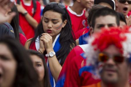 A Costa Rican fan prays during her team's penalty shootout with Greece.