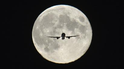 """A passenger aircraft, with the full """"Harvest Moon"""" seen behind, makes its final approach to landing at Heathrow Airport in west London, September 19, 2013. The Harvest Moon is a traditional name for the full moon that is closest to the autumn equinox, and at a traditional period where farmers would be harvesting crops. The moon's rise time and angle of path give the illusion that the Harvest Moon is both closer, larger and brighter; though actually it is not. REUTERS/Toby Melville"""