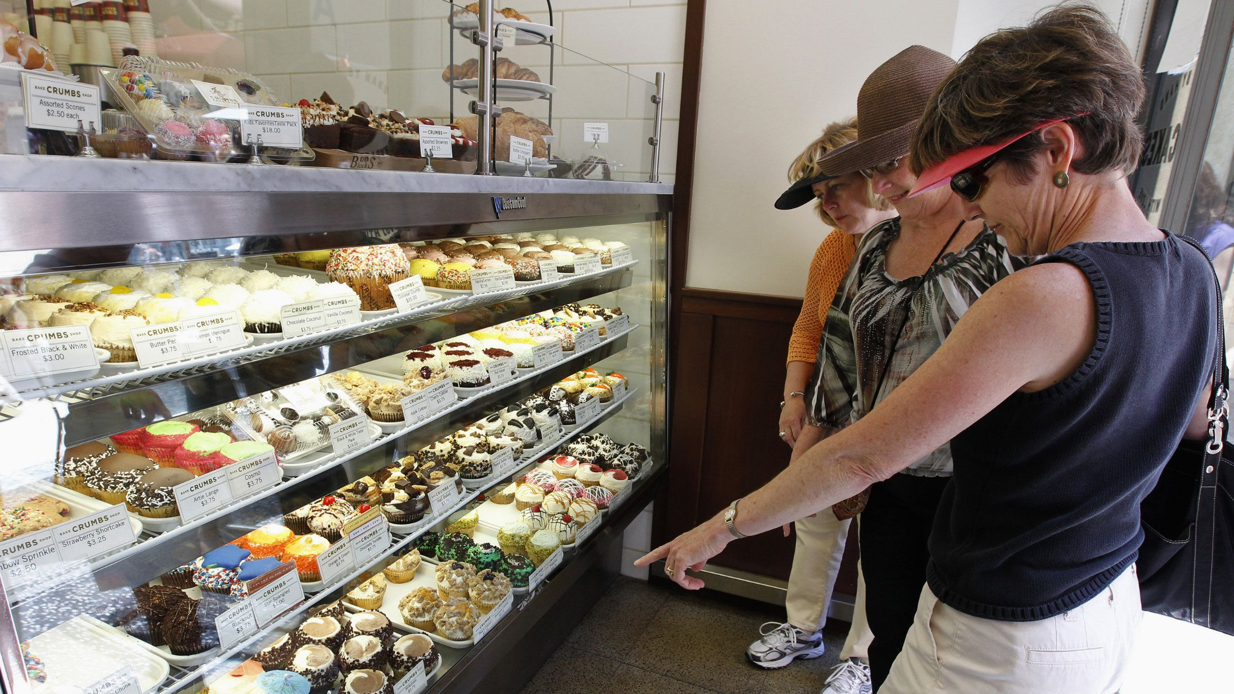 Customers Peggy Umphres (R), Barbara Frey (C) and Maureen Thompson look at cupcakes for sale in a Crumbs Bake Shop, which specializes in over 50 varieties of cupcakes, in Hollywood, California