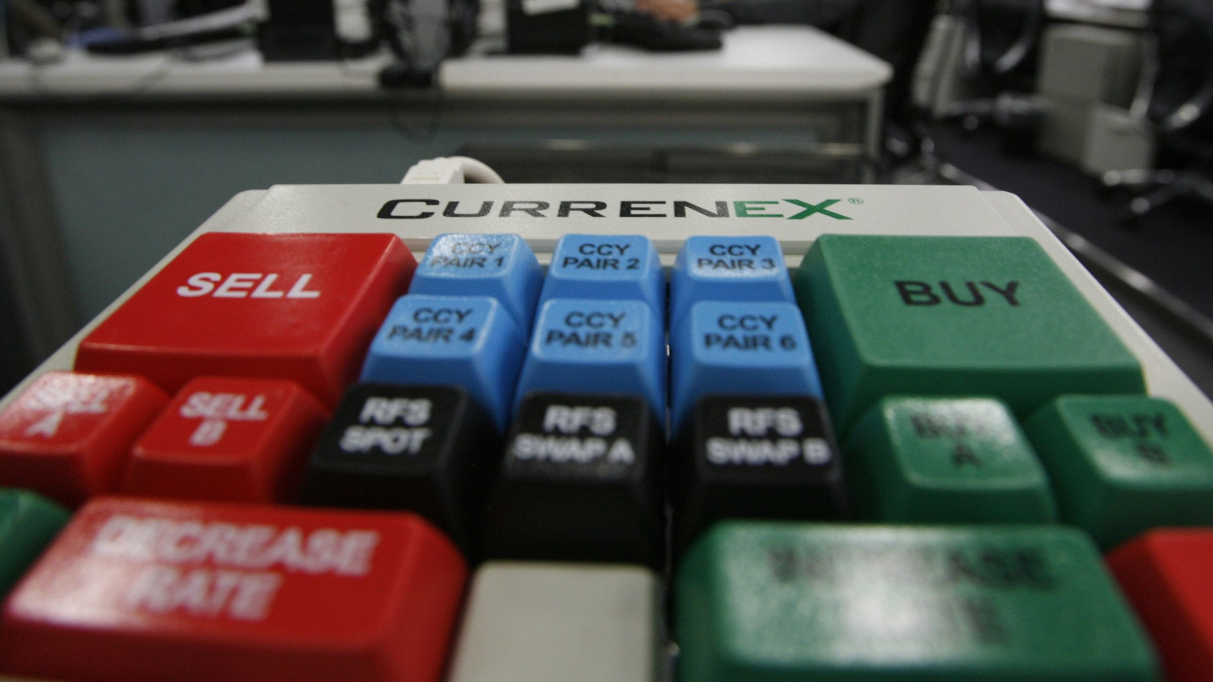 A foreign currency trading terminal keyboard is pictured in front of dealers in Tokyo