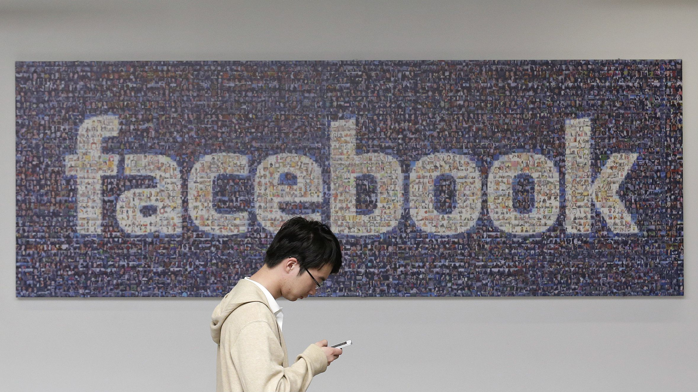 A man walks past a Facebook sign in an office on the Facebook campus in Menlo Park, Calif. British data protection authorities said Wednesday, July 2, that it is investigating revelations that Facebook conducted a psychological experiment on its users. (AP Photo/Jeff Chiu)