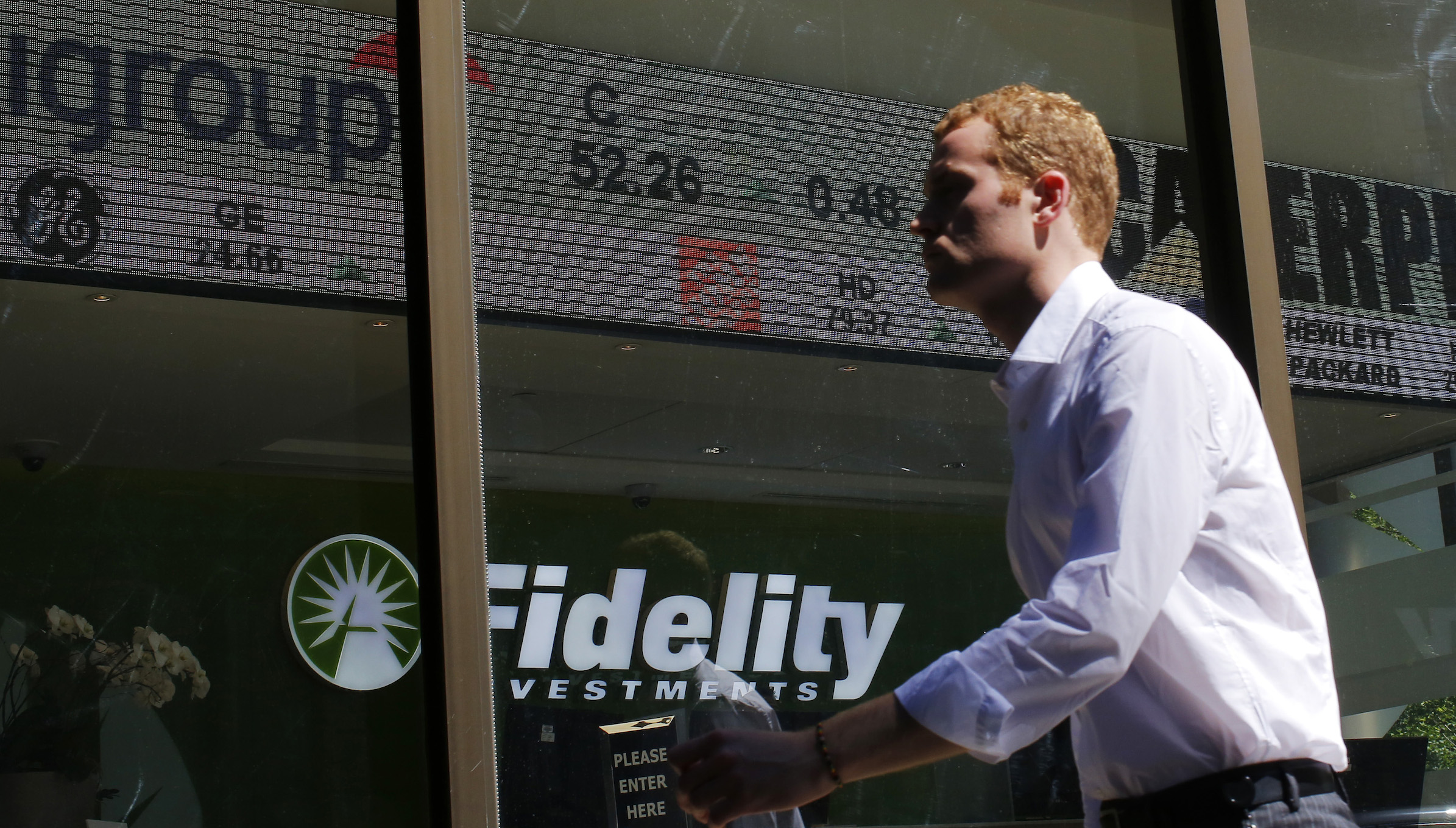 A pedestrian walks past a stock ticker at a Fidelity Investments office in Boston, Massachusetts July 31, 2013.   REUTERS/Brian Snyder (UNITED STATES - Tags: SOCIETY BUSINESS) - RTX126A0