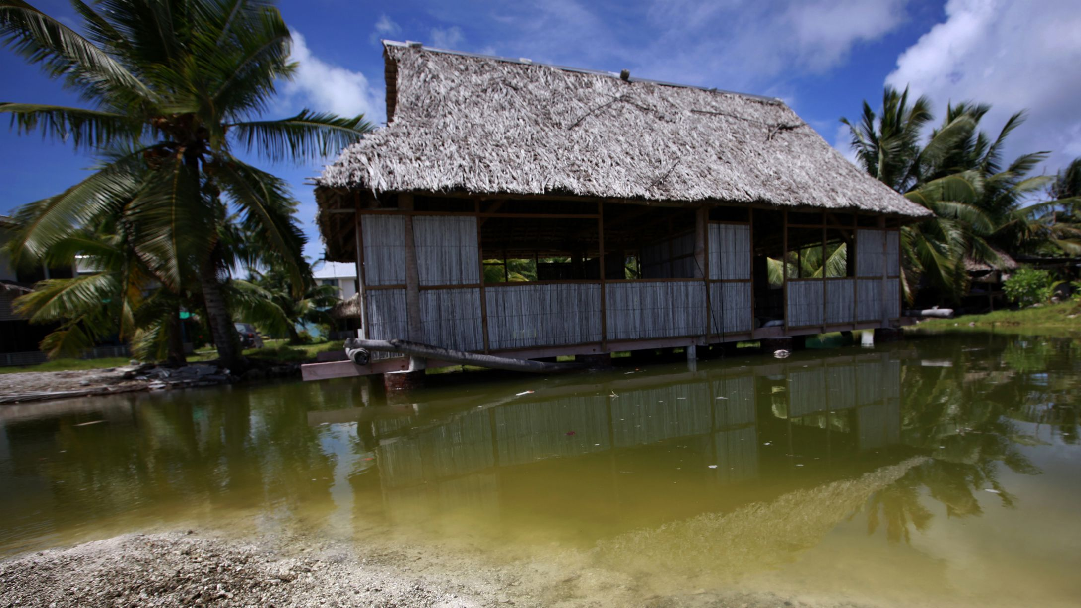 An abandoned house that is affected by seawater during high-tides stands next to a small lagoon near the village of Tangintebu on South Tarawa in the central Pacific island nation of Kiribati May 25, 2013. Kiribati consists of a chain of 33 atolls and islands that stand just metres above sea level, spread over a huge expanse of otherwise empty ocean. With surrounding sea levels rising, Kiribati President Anote Tong has predicted his country will likely become uninhabitable in 30-60 years because of inundation and contamination of its freshwater supplies. Picture taken May 25, 2013. REUTERS/David Gray
