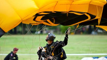 "A member of the U.S. Army's Golden Knights gathers his parachute after landing during the ""Rock Beyond Belief"" festival at Fort Bragg army base in North Carolina March 31, 2012. The atheist-themed festival drew hundreds of people to Fort Bragg on Saturday for what was believed to be the first-ever event held on a U.S. military base for service members who do not have religious beliefs. Organizers said they hoped the ""Rock Beyond Belief"" event at Fort Bragg would spur equal treatment toward nonbelievers in the armed forces and help lift the stigma for approximately 295,000 active duty personnel who consider themselves atheist, agnostic or without a religious preference."