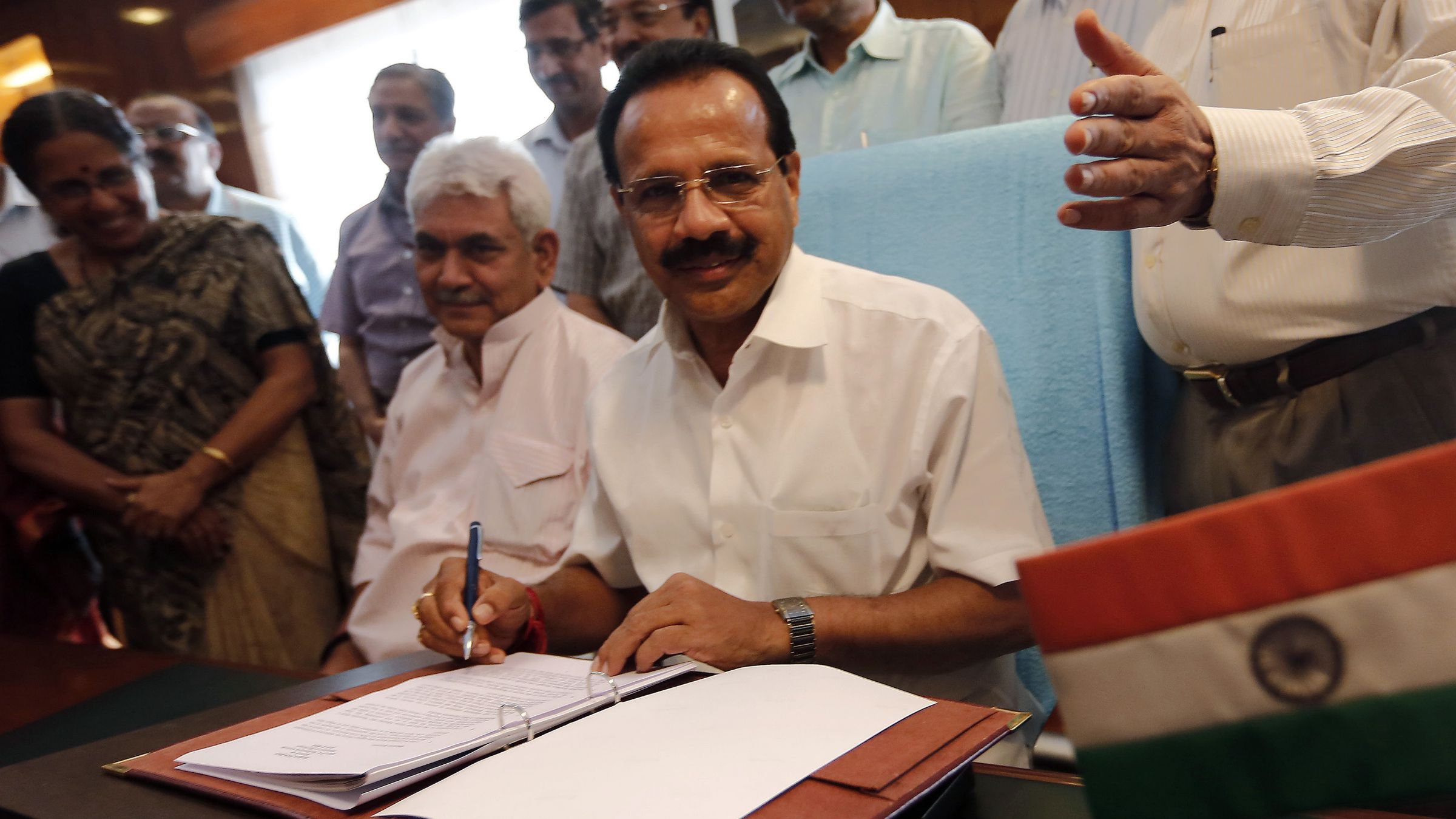India's Railway Minister Sadananda Gowda (C) poses after giving the final touches to the railway budget for the 2014/15 fiscal year, in New Delhi July 7, 2014. On Tuesday, Indian Prime Minister Narendra Modi's new government will unveil its maiden railways budget, with expectations high that he will offer bold plans to improve the service - a lifeline for 23 million Indians every day. REUTERS