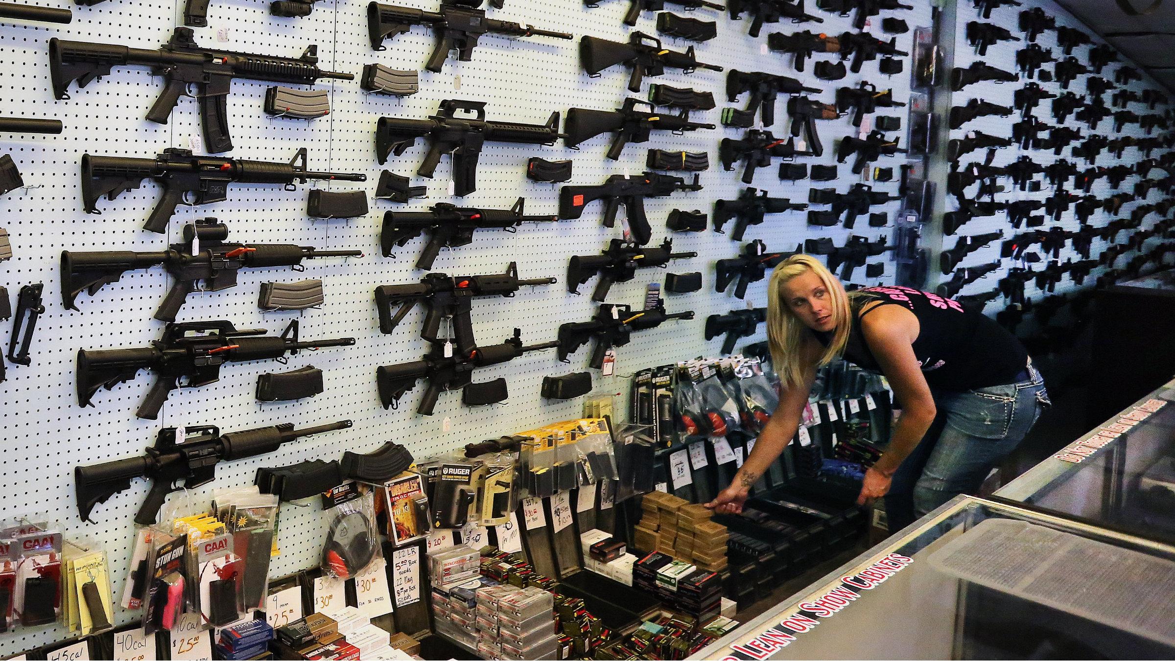 A gun store employee in Colorado helps a customer