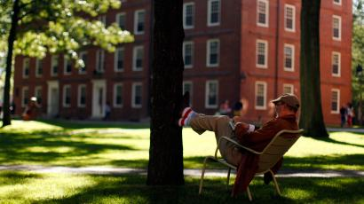 A man rests his feet on a tree in Harvard Yard at Harvard University in Cambridge, Massachusetts September 21, 2009. REUTERS/Brian Snyder (UNITED STATES) For best quality see GM1E6450PAG01.