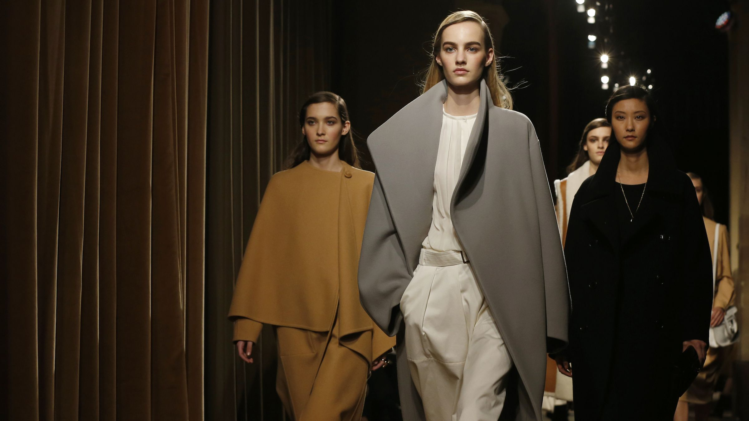 Models present creations by French designer Christophe Lemaire as part of his Fall/Winter 2014-2015 women's ready-to-wear collection for fashion house Hermes during Paris Fashion Week