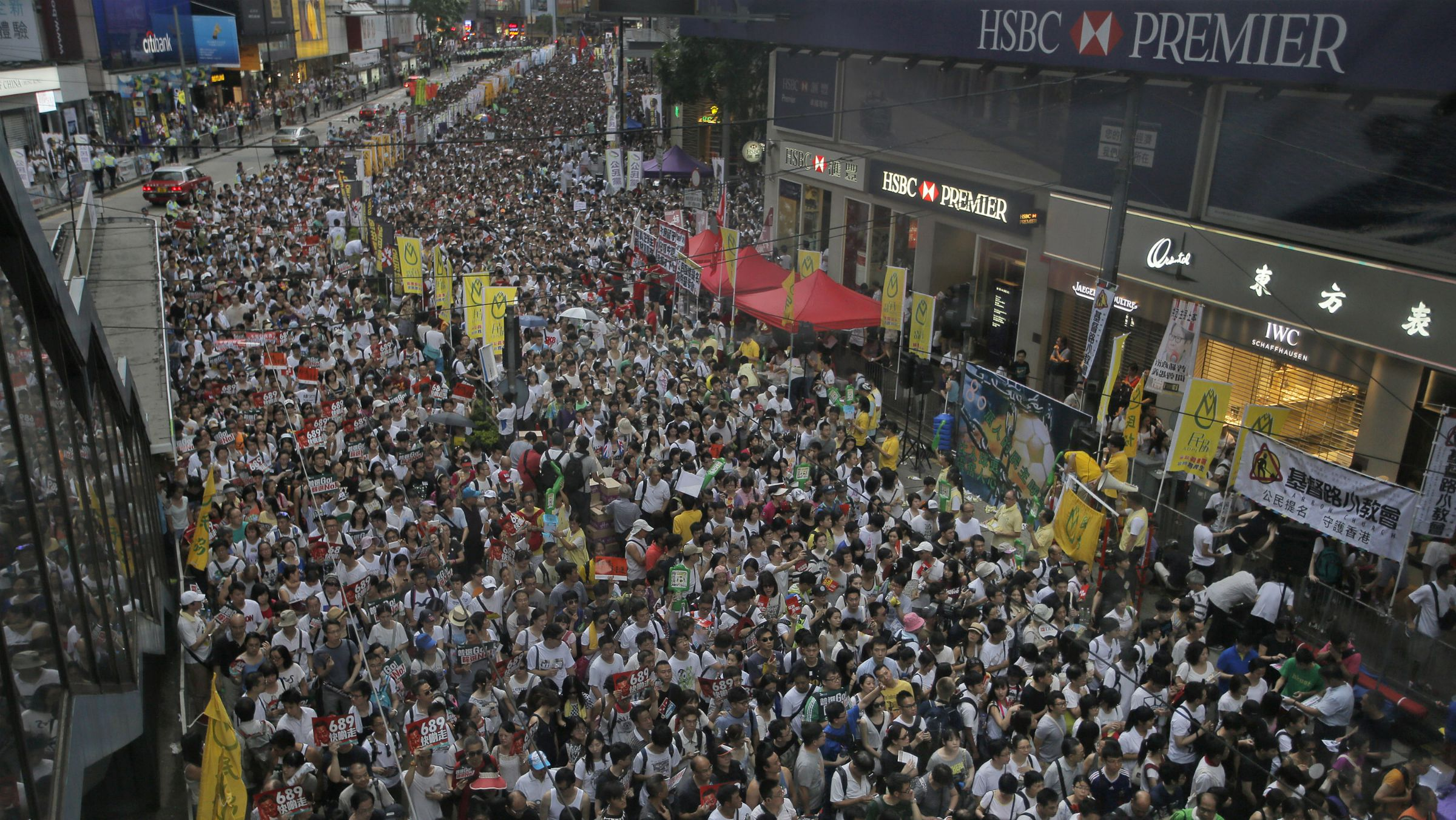 Tens of thousands of people fill in a street during a march at an annual protest in downtown Hong Kong Tuesday, July 1, 2014. Hong Kong residents marched through the streets of the former British colony to push for greater democracy in a rally fueled by anger over Beijing's recent warning that it holds the ultimate authority over the southern Chinese financial center. The protest comes days after nearly 800,000 residents voted in a mock referendum aimed at bolstering support for full democracy. (AP Photo/Vincent Yu