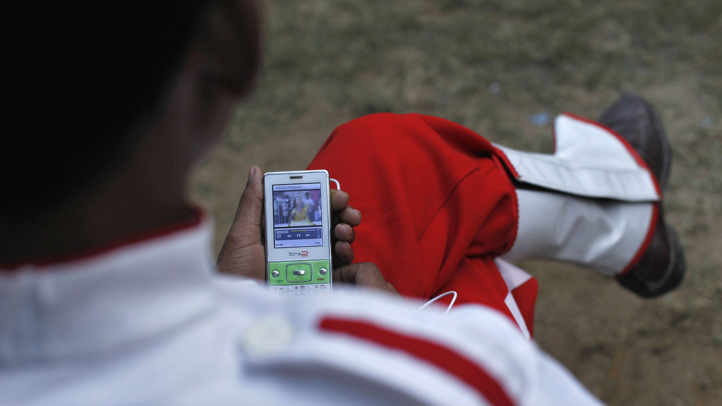 A member of a brass band watches a video clip on his mobile phone as he waits to perform at a wedding procession in New Delhi November 24, 2012. T