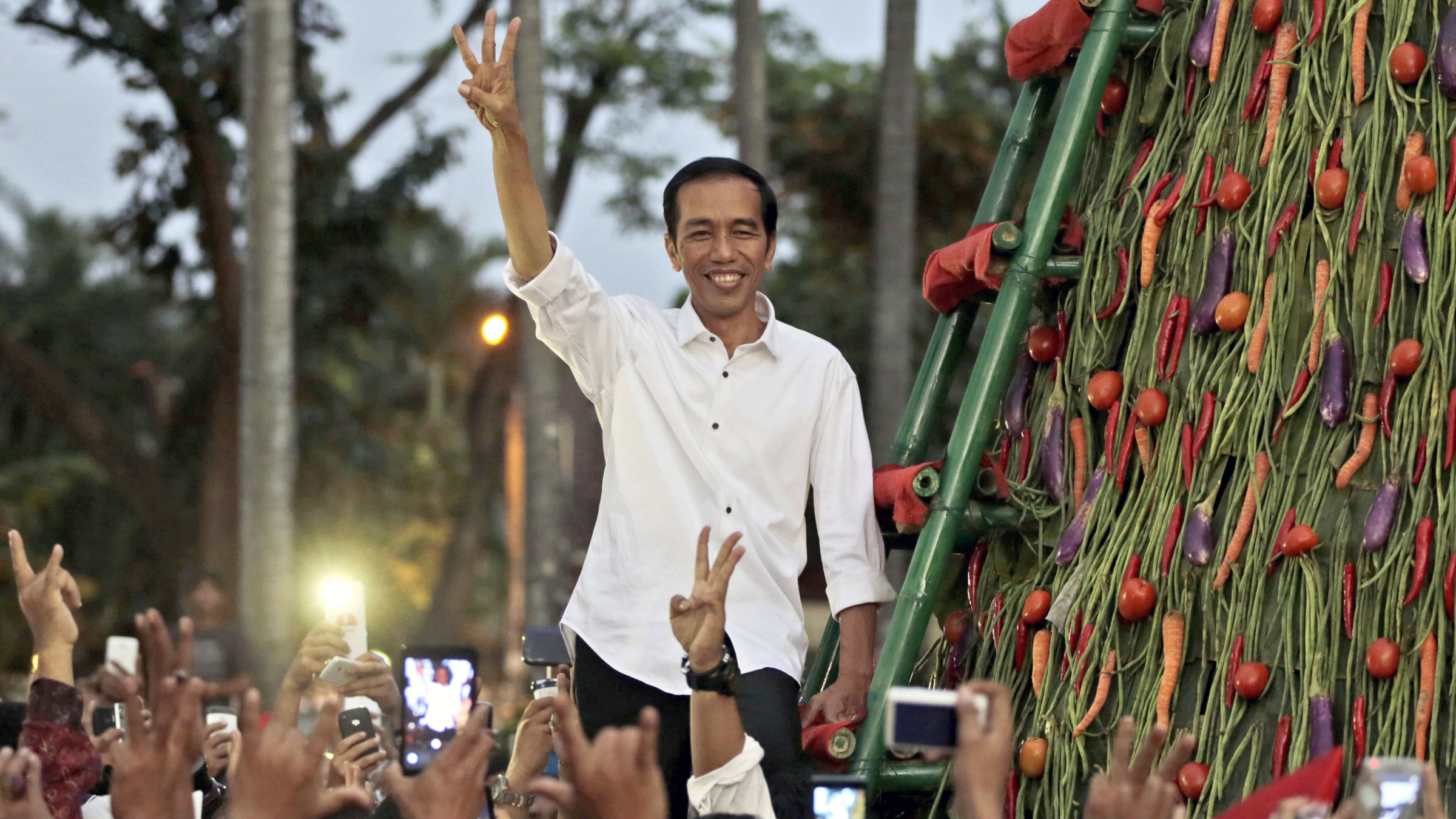 Indonesian president-elect Joko Widodo greets supporters with his 'three-finger greeting' symbolizing the third of Indonesia's five principles.