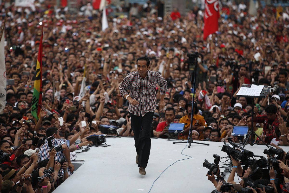 """Indonesian presidential candidate Joko """"Jokowi"""" Widodo runs on the stage after delivering a speech in front of his supporters at Gelora Bung Karno stadium in Jakarta July 5, 2014."""