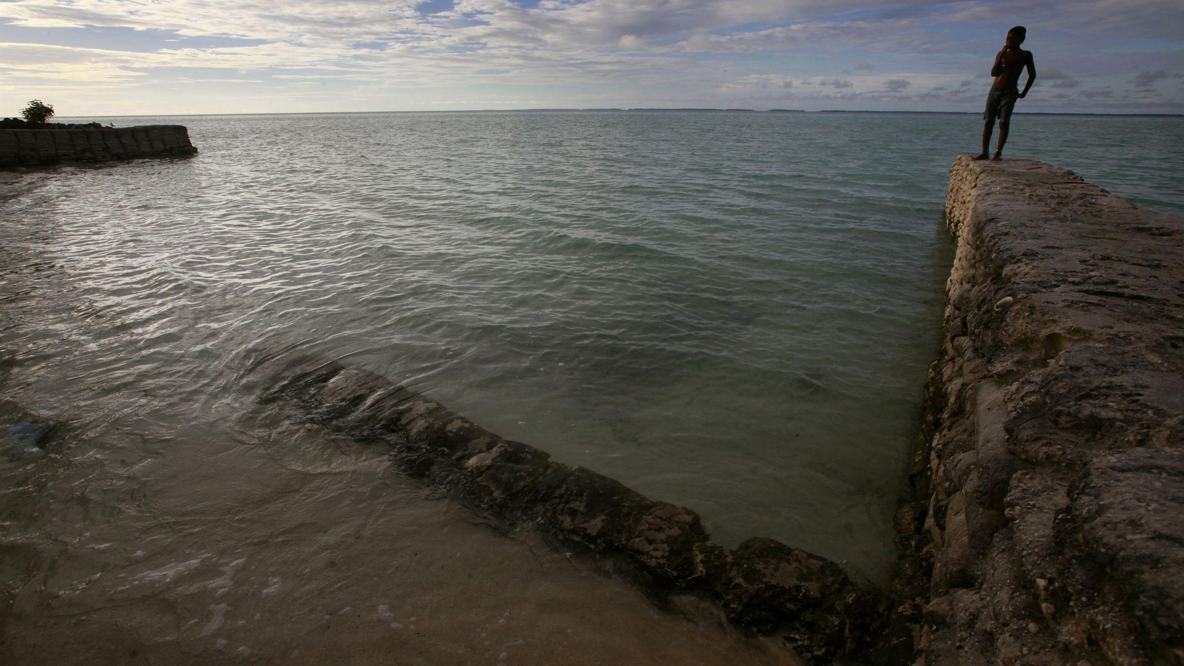 kiribati climate change global warming sea level rise atoll A boy stands on top of a sea-wall near the village of Tangintebu on South Tarawa in the central Pacific island nation of Kiribati May 26, 2013. REUTERS/David Gray