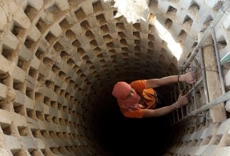 A Palestinian smuggler climbs down into a tunnel, temporarily closed by Hamas forces, beneath the Egyptian-Gaza border in Rafah in the southern Gaza Strip April 14, 2010. Israel wants to close down the smuggling tunnels between Egypt and the Gaza Strip, but the tunnelers have become so good it's now possible to drive a car through them, literally.