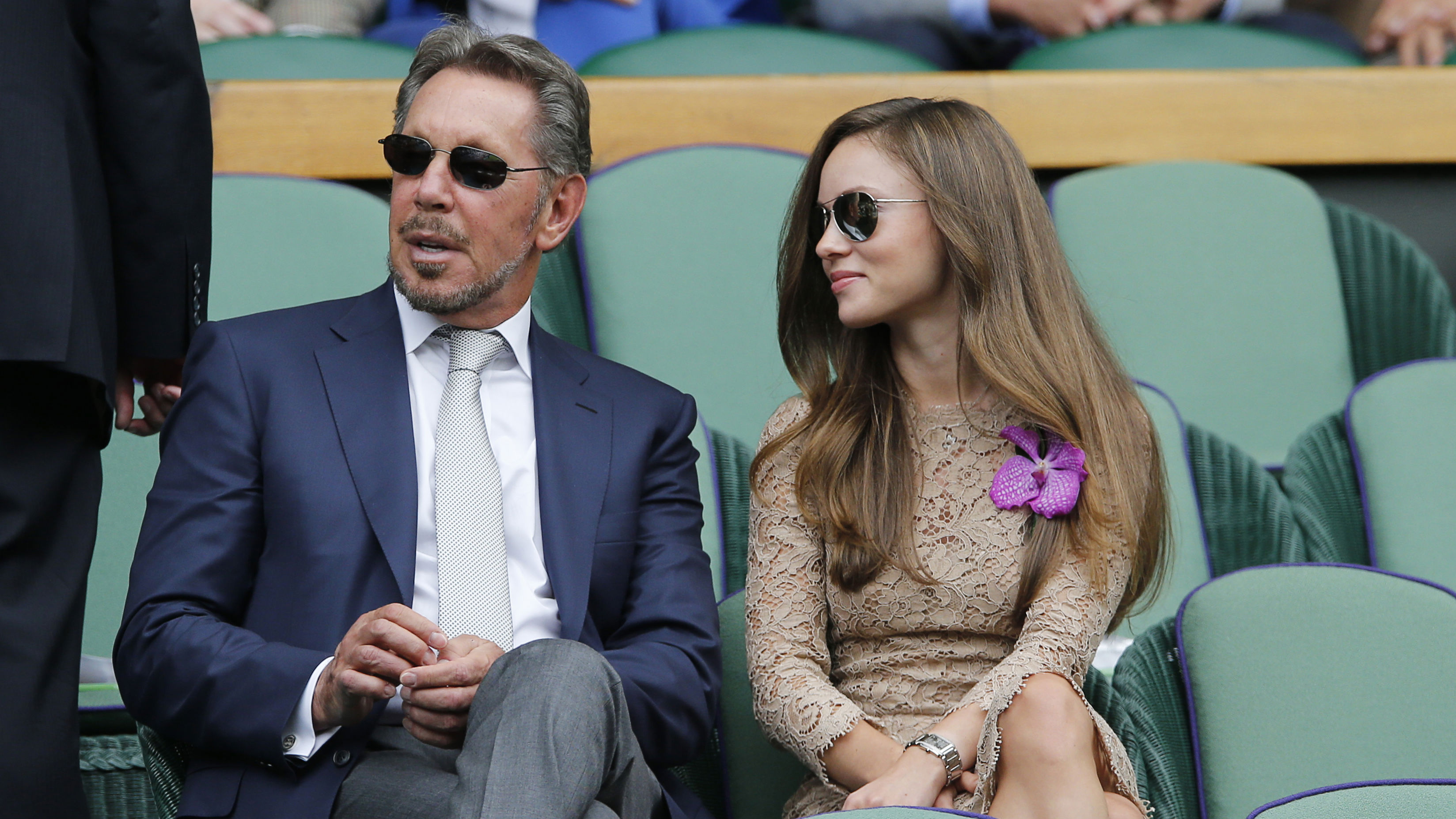 Larry Ellison, left, and Nikita Kahn take their seats in the Royal Box prior to the men's singles final between Roger Federer of Switzerland and Novak Djokovic of Serbia on centre court at the All England Lawn Tennis Championships in Wimbledon, London, Sunday July 6, 2014. (AP Photo/Ben Curtis)
