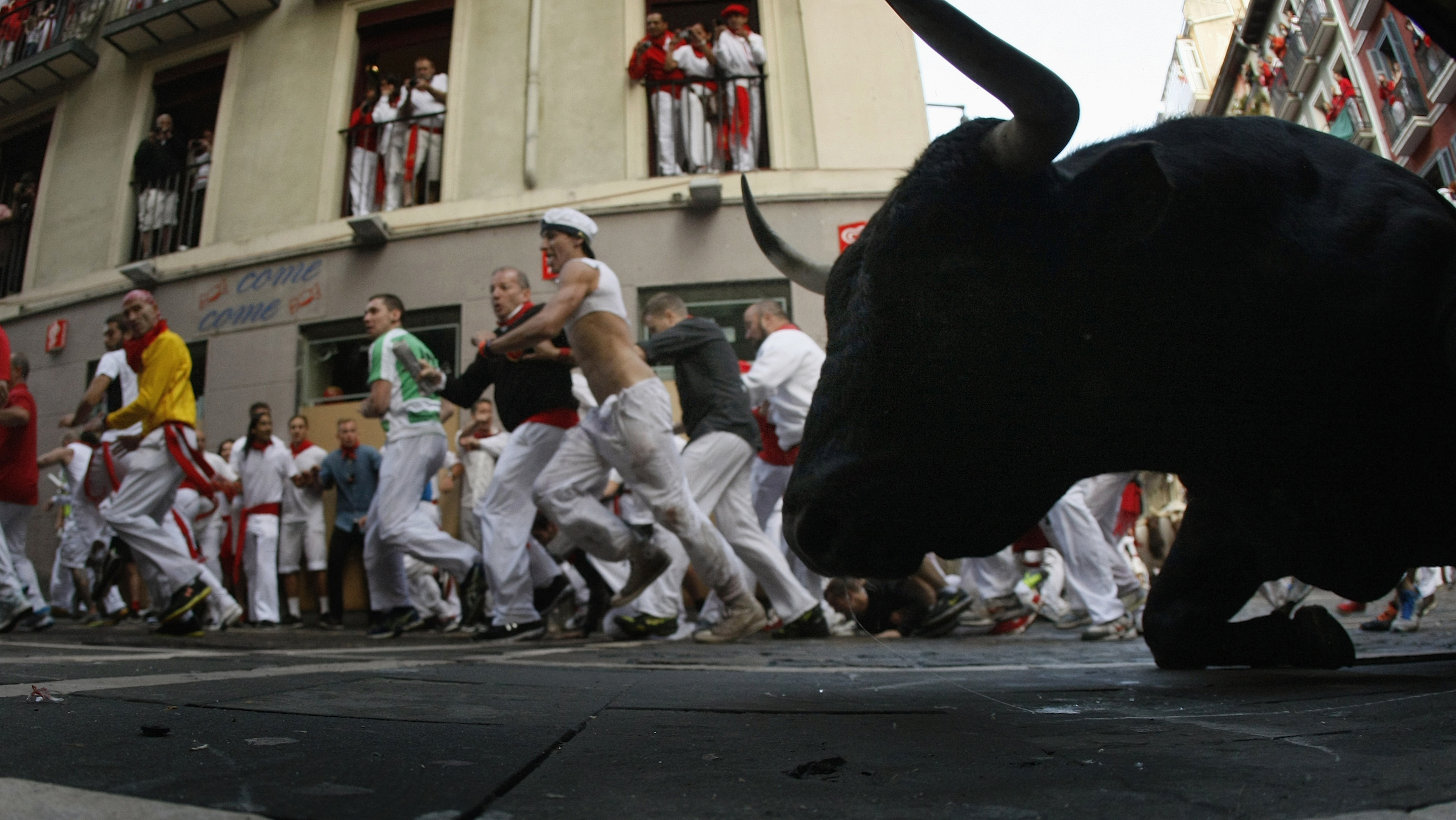 A Dolores Aguirre fighting bull falls at the Estafeta corner, during the second running of the bulls of the San Fermin festival in Pamplona July 8, 2014. Two runners were hospitalized following a run that lasted two minutes and twenty seconds, according to local media. REUTERS/Eloy Alonso (SPAIN - Tags: SOCIETY ANIMALS) - RTR3XK7E