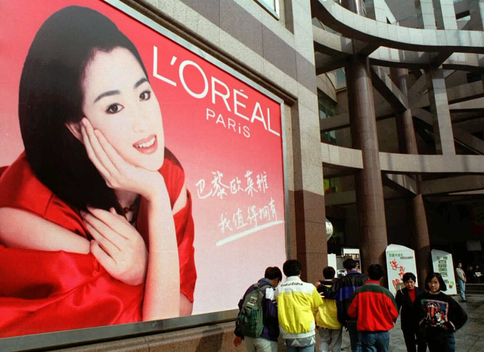 People walk past a giant billboard with a picture of popular Chinese actress Gong Li, advertizing French cosmetics, at the Parkson Shopping Center in Shanghai Sunday, Nov. 23, 1997. (AP Photo/Xinhua, Hu Haixing)