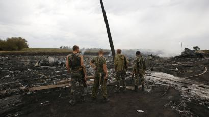 Armed pro-Russian separatists stand at the site of a Malaysia Airlines Boeing 777 plane crash