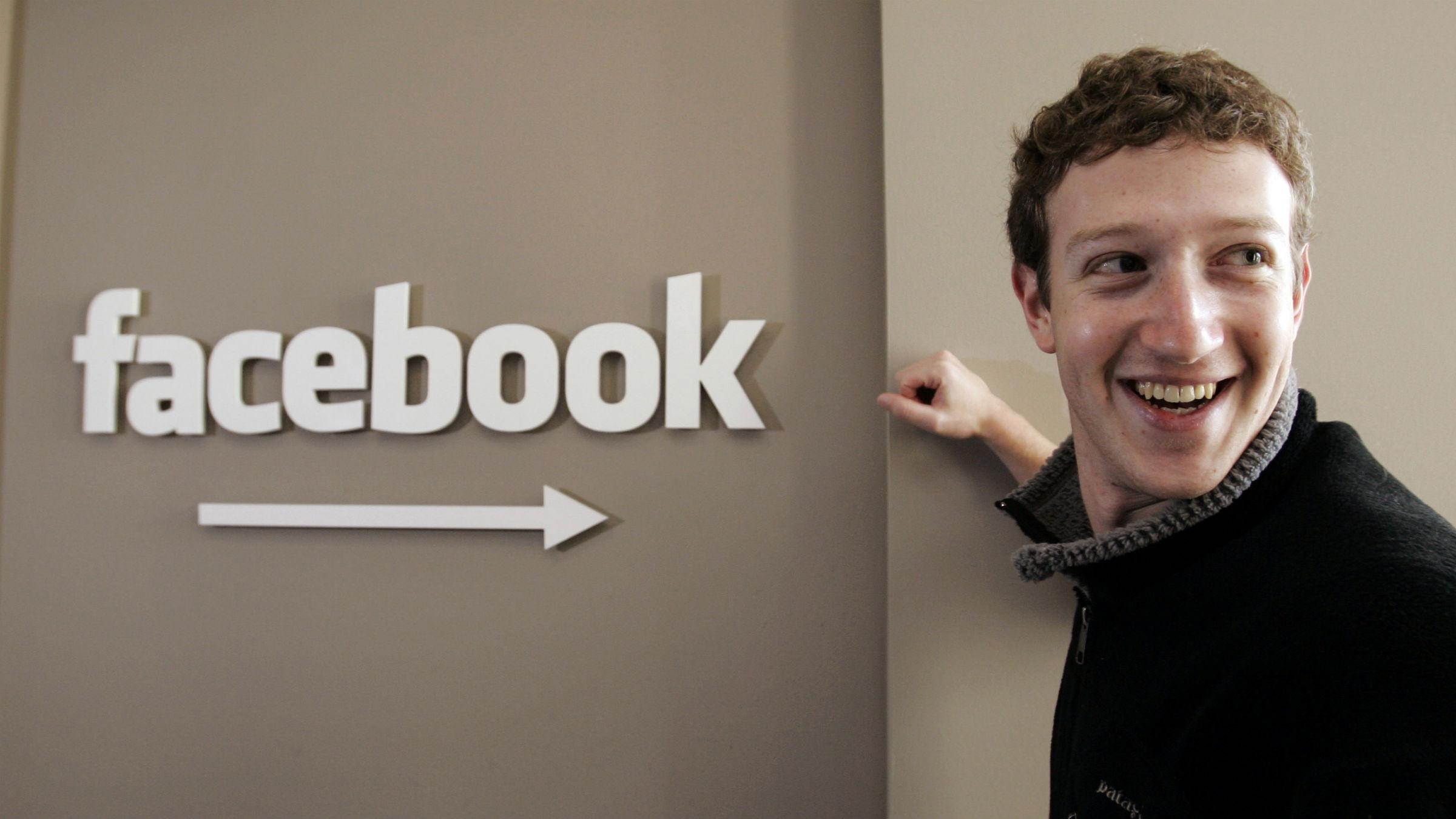 Mark Zuckerberg standing in front of Facebook sign