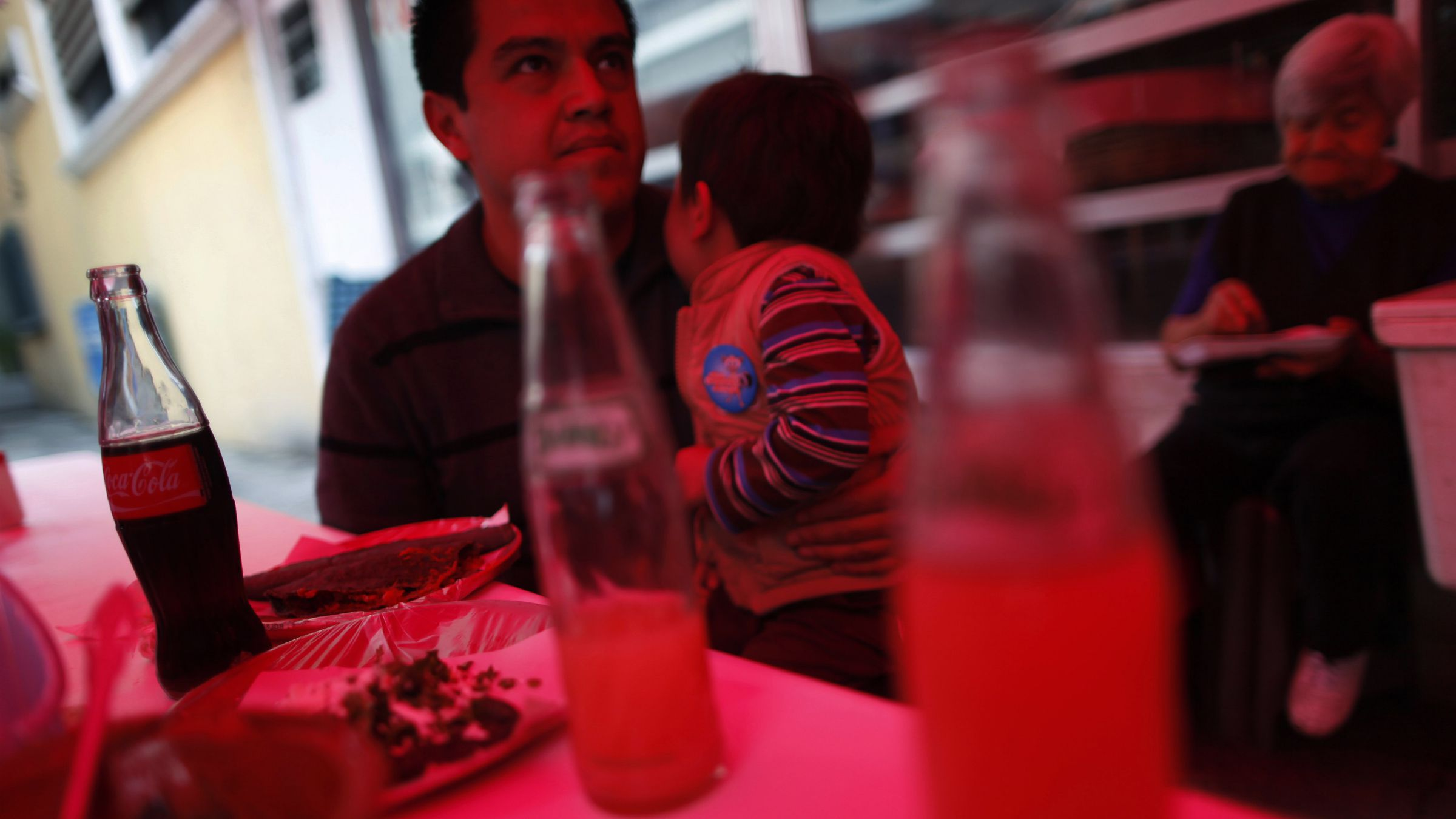 A man and a child eat next to bottled drinks at a food stand in Mexico City September 10, 2013. Mexico's President Enrique Pena Nieto's tax reform proposals appear toughest on Mexico's bottlers, who would be hit by a levy that the government hopes will collect close to $1 billion a year. The government plans to apply a 1 peso per liter ($0.076) excise on sugary drinks, weighing on bottlers like Coca-Cola FEMSA