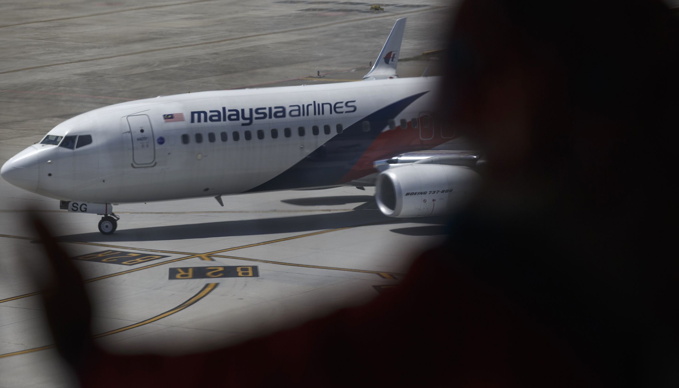 "A woman looks at a Malaysia Airline aircraft sitting on the tarmac at a viewing gallery in Kuala Lumpur International Airport in Sepang July 19, 2014. U.S. President Barack Obama said the downing of a Malaysian jetliner in a Ukrainian region controlled by Russian-backed separatists should be a ""wake-up call for Europe and the world"" in a crisis that appears to be at a turning point and warned Russia of possible tightening of sanctions. While stopping short of blaming Russia for Thursday's crash of Malaysia Airlines Flight MH17, in which 298 people died, Obama accused Moscow of failing to stop the violence that made it possible to shoot down the plane. REUTERS/Athit Perawongmetha (MALAYSIA - Tags: TRANSPORT DISASTER) - RTR3ZAXZ"
