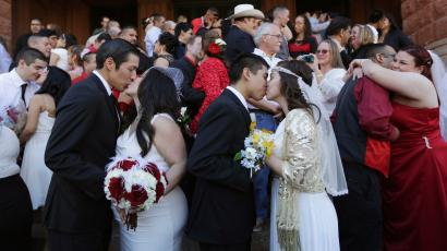 Anthony Sanchez and Stephanie Hernandez, left, and John and Analicia Vazquez, right, kiss after taking their vows with dozens of other couples in a mass Valentine's Day wedding on the steps of the Bexar County Courthouse, Friday, Feb. 14, 2014, in San Antonio. (AP Photo/Eric Gay)