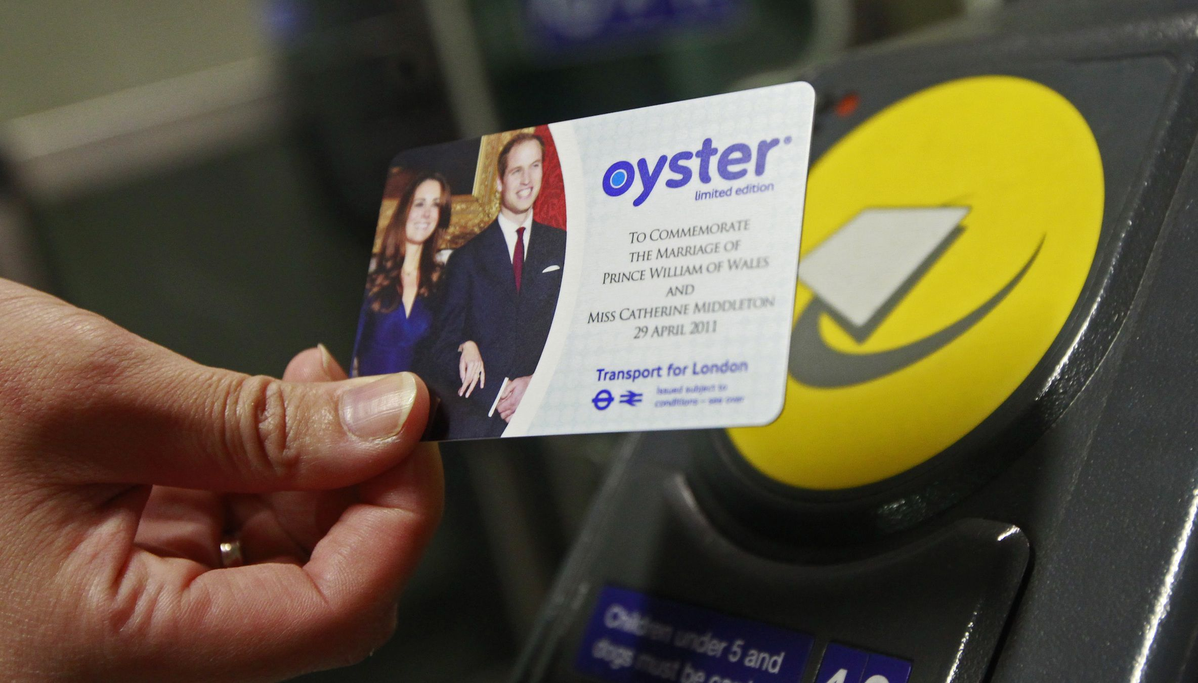 A tube passenger holds a royal wedding commemorative Oyster card, bearing an image of Britain's Prince William and his fiancee Kate Middleton, at an entrance barrier in King's Cross station in London April 21, 2011. 750,000 of the cards which are a commemorative version of the widely used electronic device used to pay for train and bus tickets in London, went on sale on Thursday. REUTERS/Luke MacGregor   (BRITAIN - Tags: ENTERTAINMENT TRAVEL ROYALS SOCIETY) - RTR2LH1X