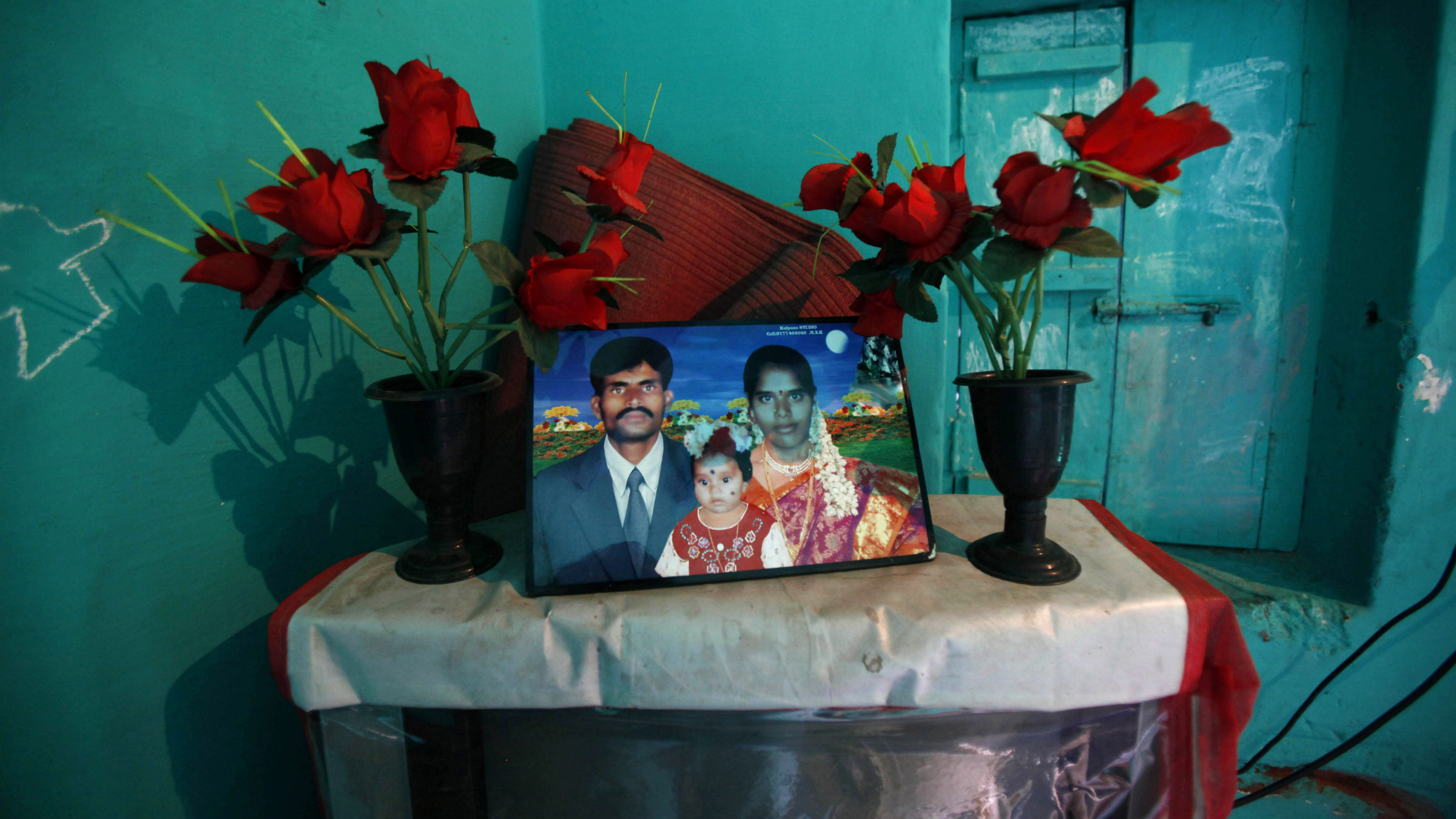 In this photo taken Feb. 14, 2012, a portrait of debt-ridden Jayaramappa, who hanged himself in his home on Oct. 4, 2010, and his family stands on top of a television set inside their house in Madakasira village about 145 kilometers (90 miles) north of Bangalore, India. A wave of suicides among the impoverished residents of India's Andhra Pradesh state was blamed on the relentless tactics of agents from microfinance companies, which give small loans intended to lift up the very poor.