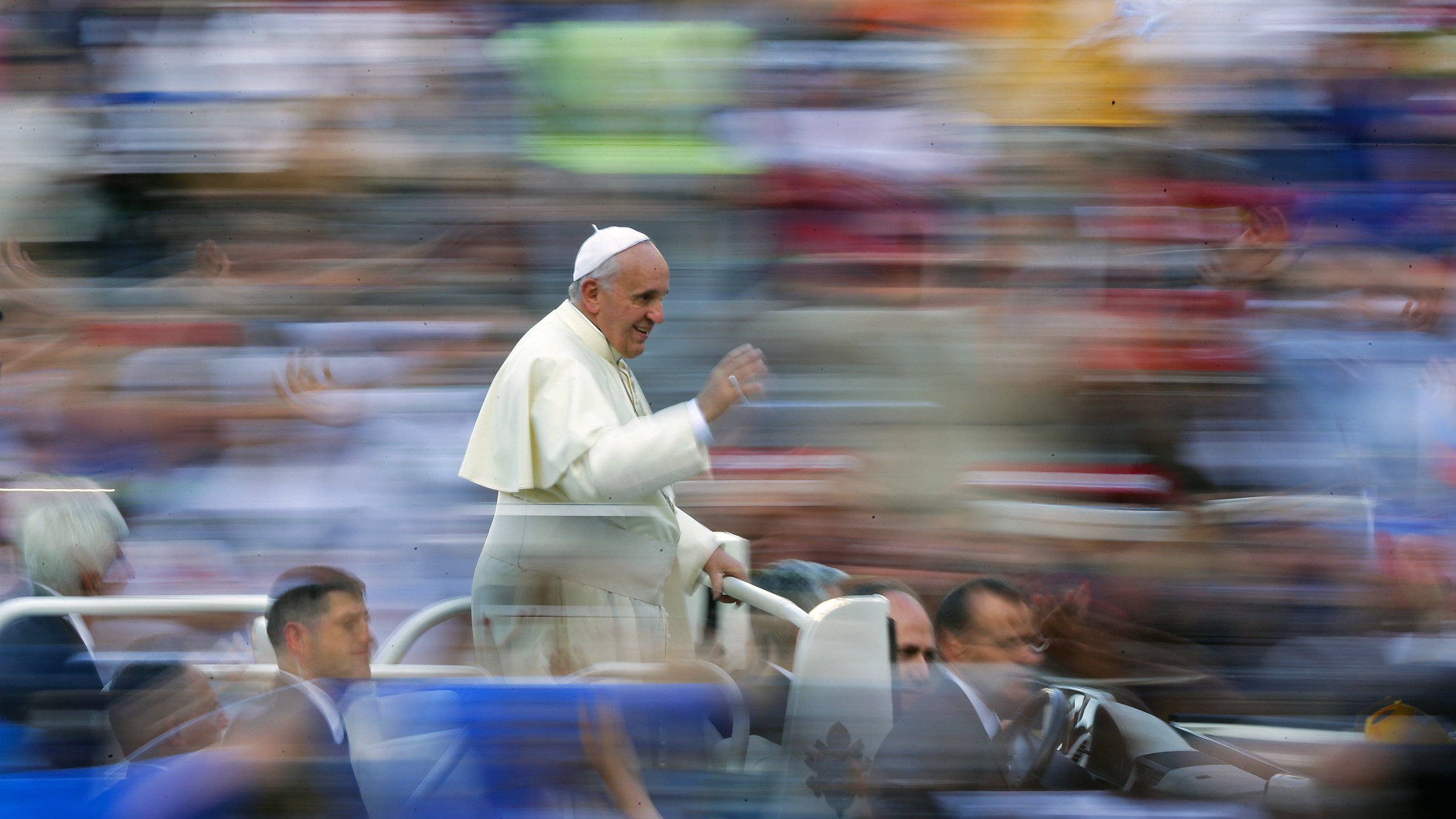 Pope Francis in a fast-moving popemobile shot.