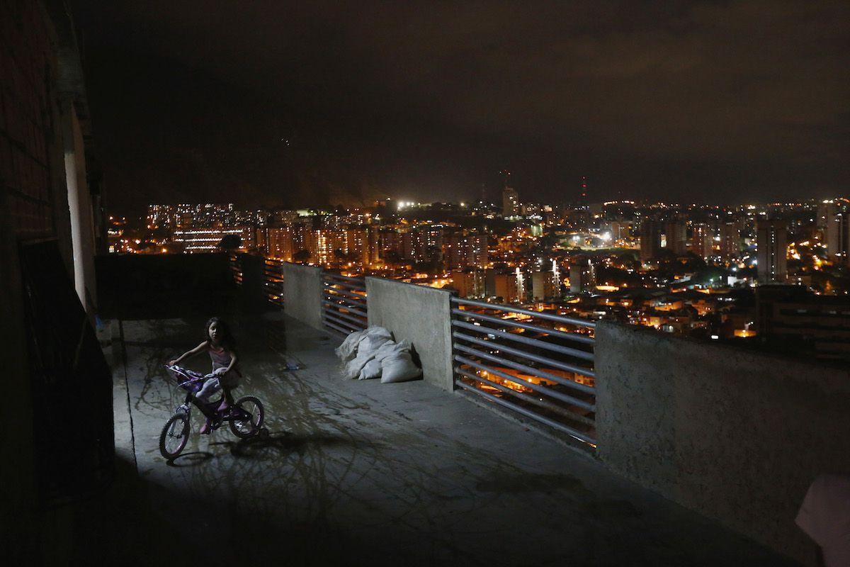 A girl rides her bike in Caracas's vertical slum Torre David