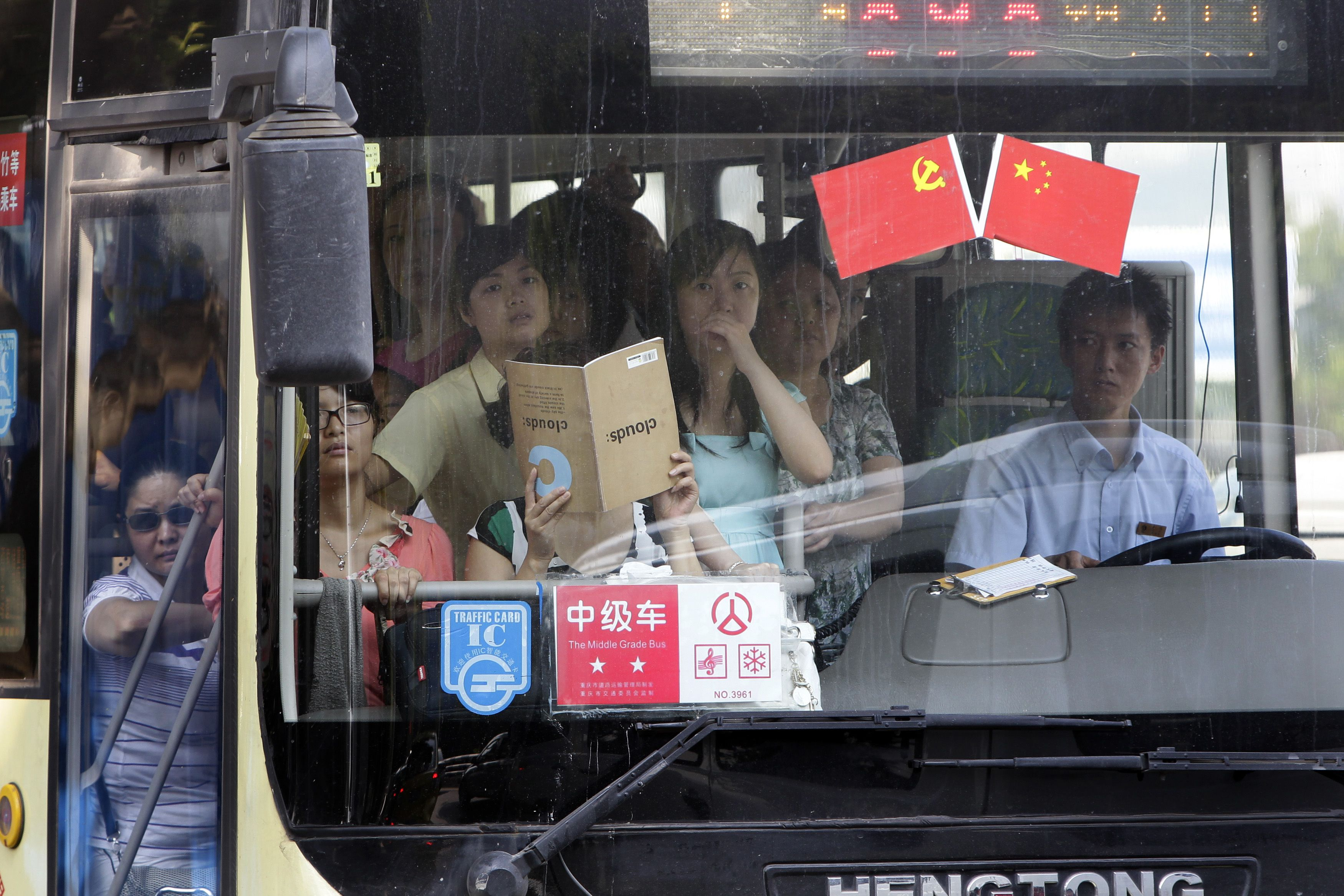 Passengers stand in a crowded bus decorated with Chinese national and communist party flags to celebrate the upcoming 90th anniversary of the founding of the Communist Party of China (CPC) in Chongqing municipality June 30, 2011