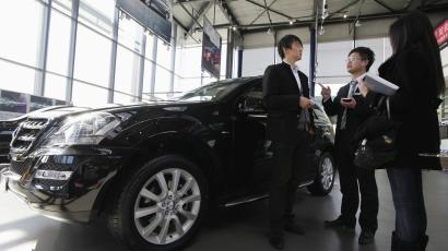 A salesperson speaks to a customer next to a Mercedes-Benz ML 350 car displayed at a dealership in Beijing.