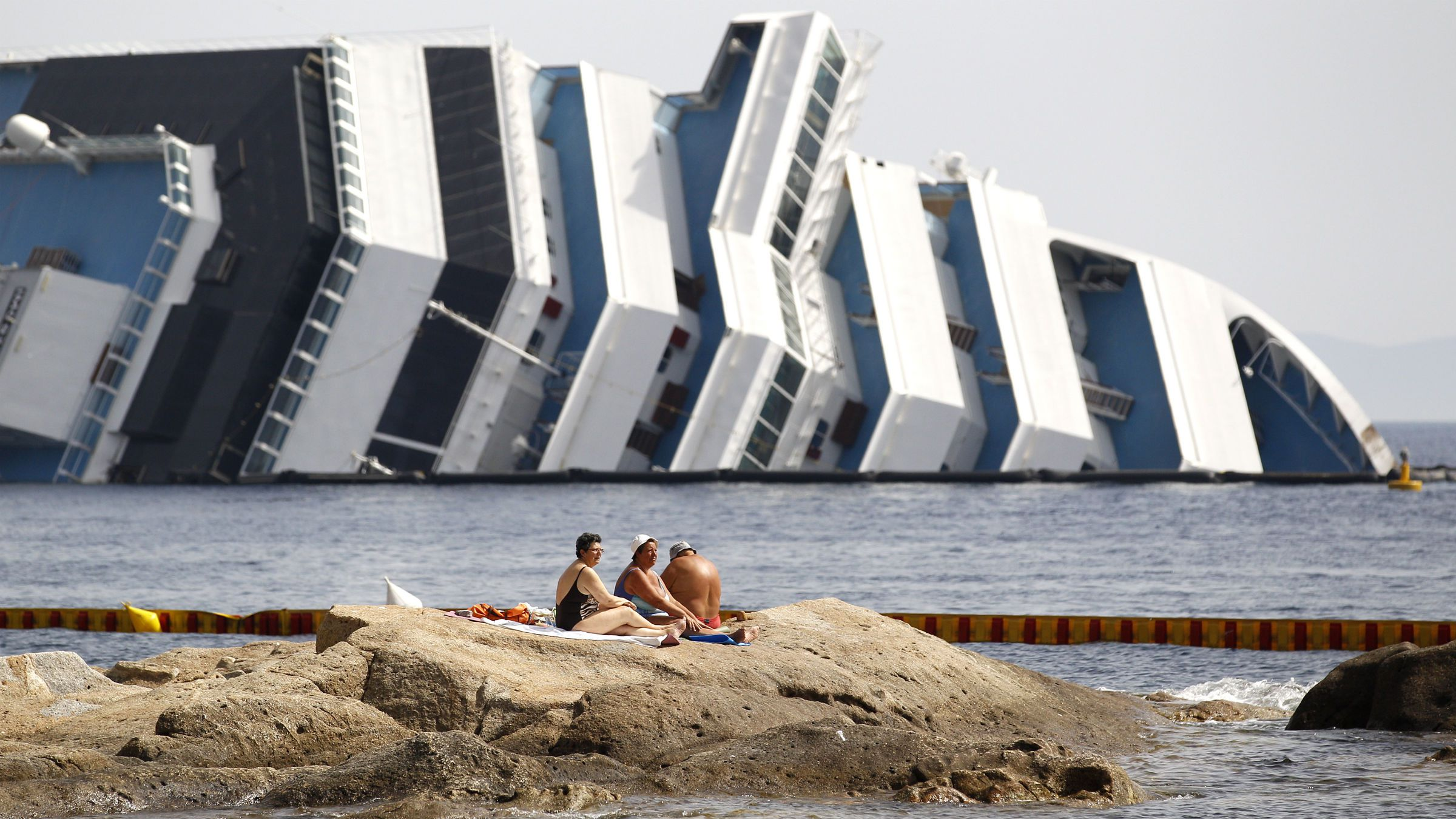 Vacationers bask in front of the wreckage of capsized cruise liner Costa Concordia near the harbour of Giglio Porto June 20, 2012. The salvage operation to move the capsized Costa Concordia away from the island of Giglio, where it ran aground three months ago, will begin in June. REUTERS/Max Rossi