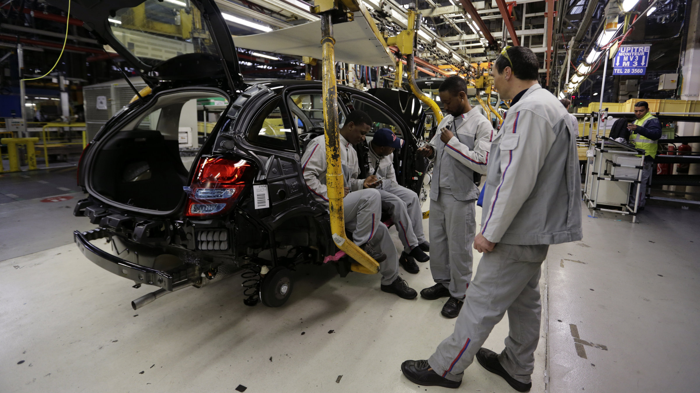Workers gather around an unfinished automobile on the assembly line at the PSA-Peugeot Citroen plant in Aulnay-sous-Bois, near Paris.