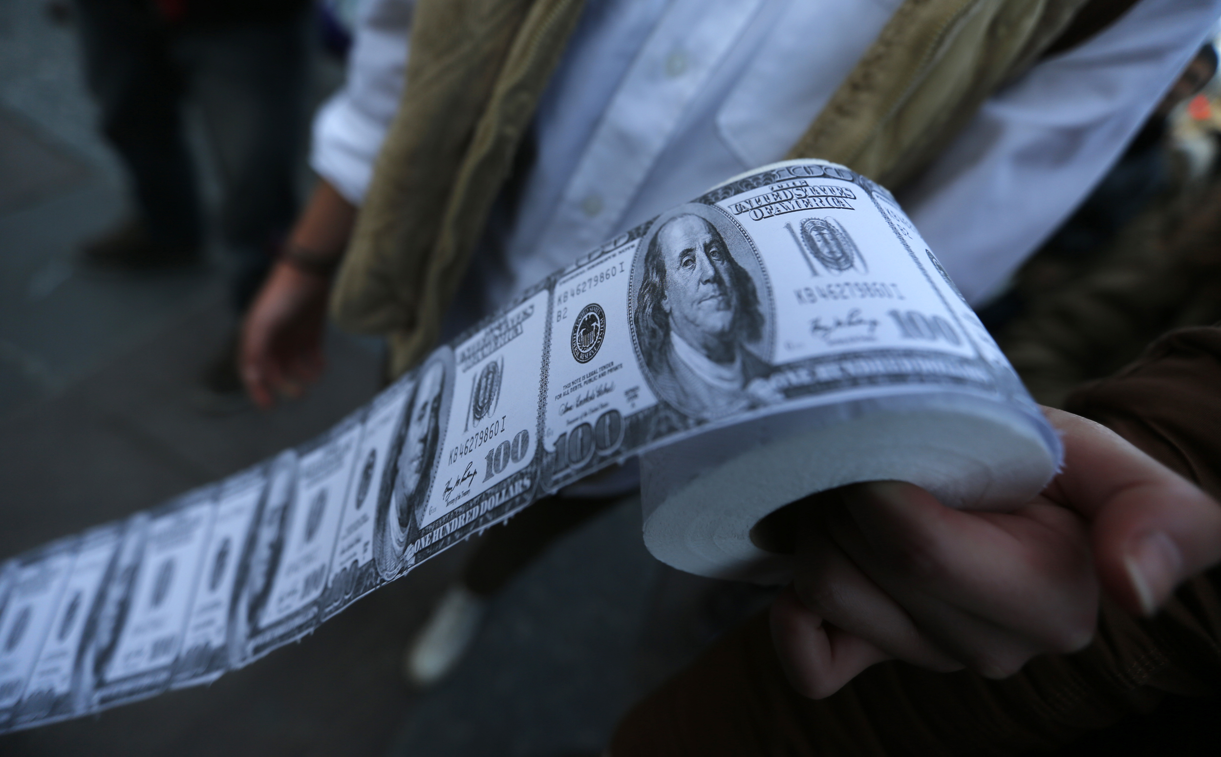 A demonstrator holds toilet paper made from fake U.S. dollars during a protest.