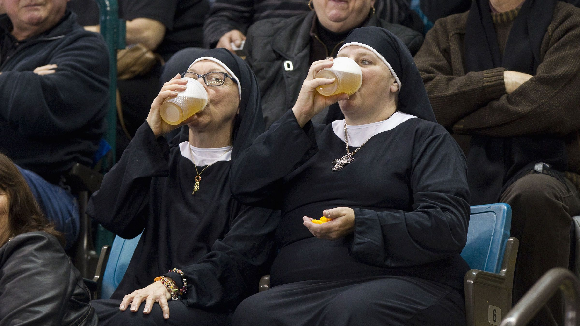 Two women wearing nun outfits drink beer while watching the playoff draw between Quebec and Manitoba at the 2014 Tim Hortons Brier curling championships in Kamloops, British Columbia March 8, 2014. REUTERS/Ben Nelms (CANADA - Tags: SPORT CURLING SOCIETY TPX IMAGES OF THE DAY)