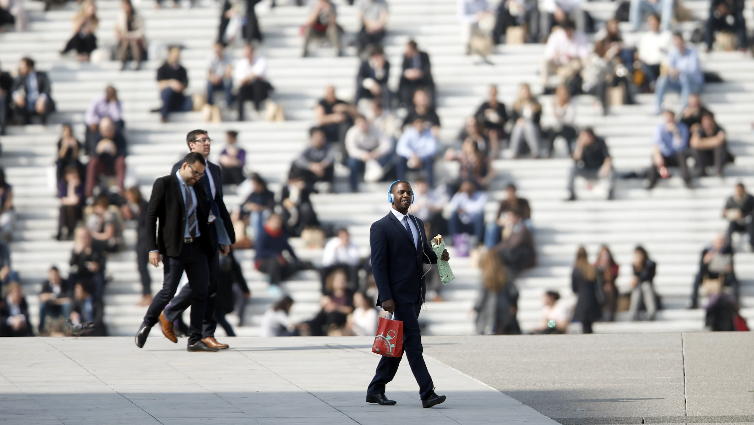 Businessmen enjoy the good weather at lunch time under the Arche de la Defense, in the financial and business district west of Paris, as warm and sunny weather continues in France, March 13, 2014. Residents and visitors to Paris basking in a streak of unseasonable sunshine were also being treated with a dangerous dose of particles from car fumes that pushed air pollution to levels above other northern European capitals this week. Swathes of France, including the French capital, were on maximum alert over air pollution on Thursday, prompting Paris authorities to make green transportation such as its Velib bike-share and the Autolib electric car fleet free for the day. REUTERS/Charles Platiau (FRANCE - Tags: BUSINESS ENVIRONMENT SOCIETY TPX IMAGES OF THE DAY) - RTR3GYRI