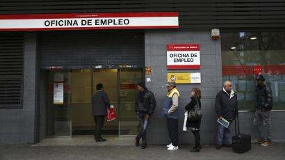 People wait to enter a government-run employment office in Madrid.