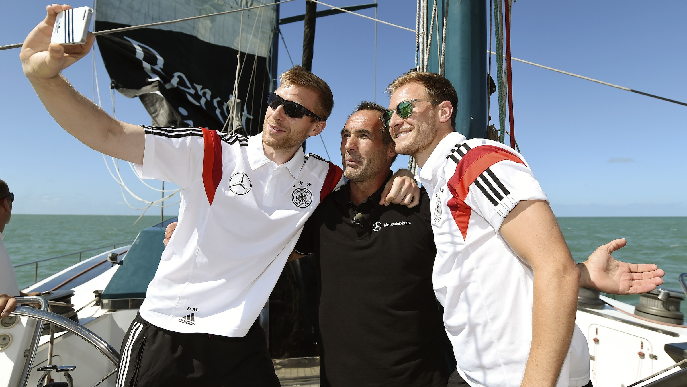 Germany's national soccer team players Per Mertesacker (L) and Benedikt Hoewedes (R) take a picture together with explorer and adventurer Mike Horn of Switzerland (C) aboard the sailing ship 'Pangaea' near Santo Andre village, near Porto Seguro June 10, 2014. REUTERS/Markus Gilliar/Pool (BRAZIL - Tags: SPORT SOCCER WORLD CUP ) - RTR3T4PR