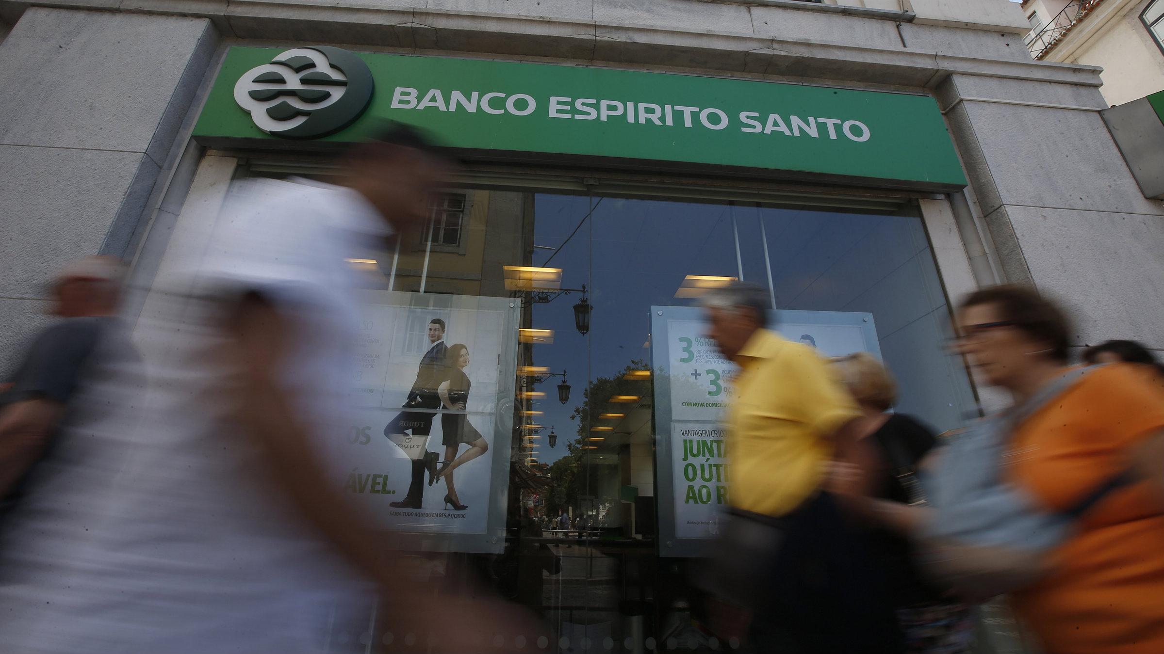 People walk past an office of Portuguese bank Banco Espirito Santo in Lisbon