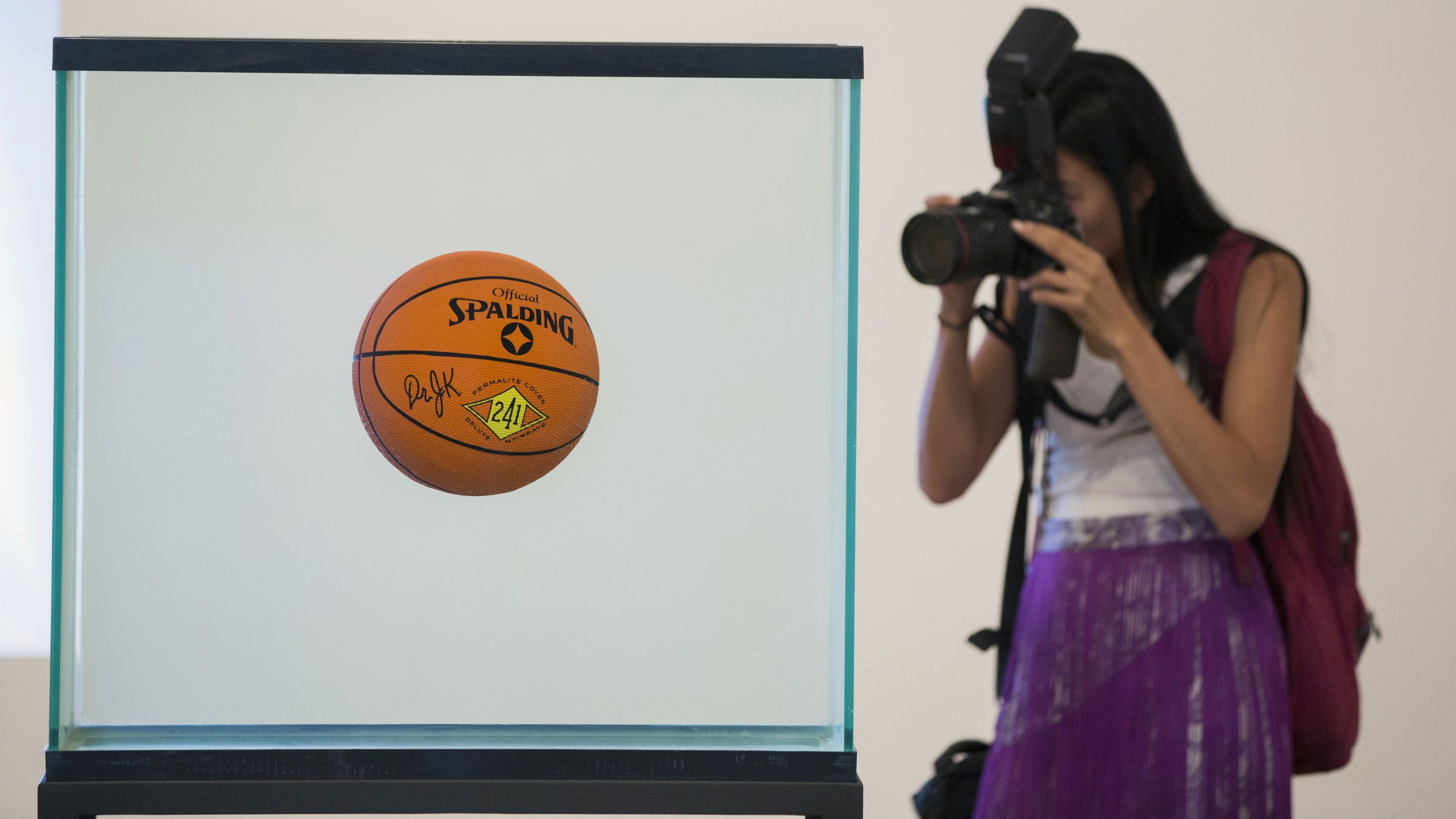 A woman photographs the sculpture One Ball Total Equilibrium Tank during a media preview before the opening of a Jeff Koons retrospective at the Whitney Museum of American Art in New York June 24, 2014. REUTERS/Lucas Jackson (UNITED STATES - Tags: SOCIETY ENTERTAINMENT)