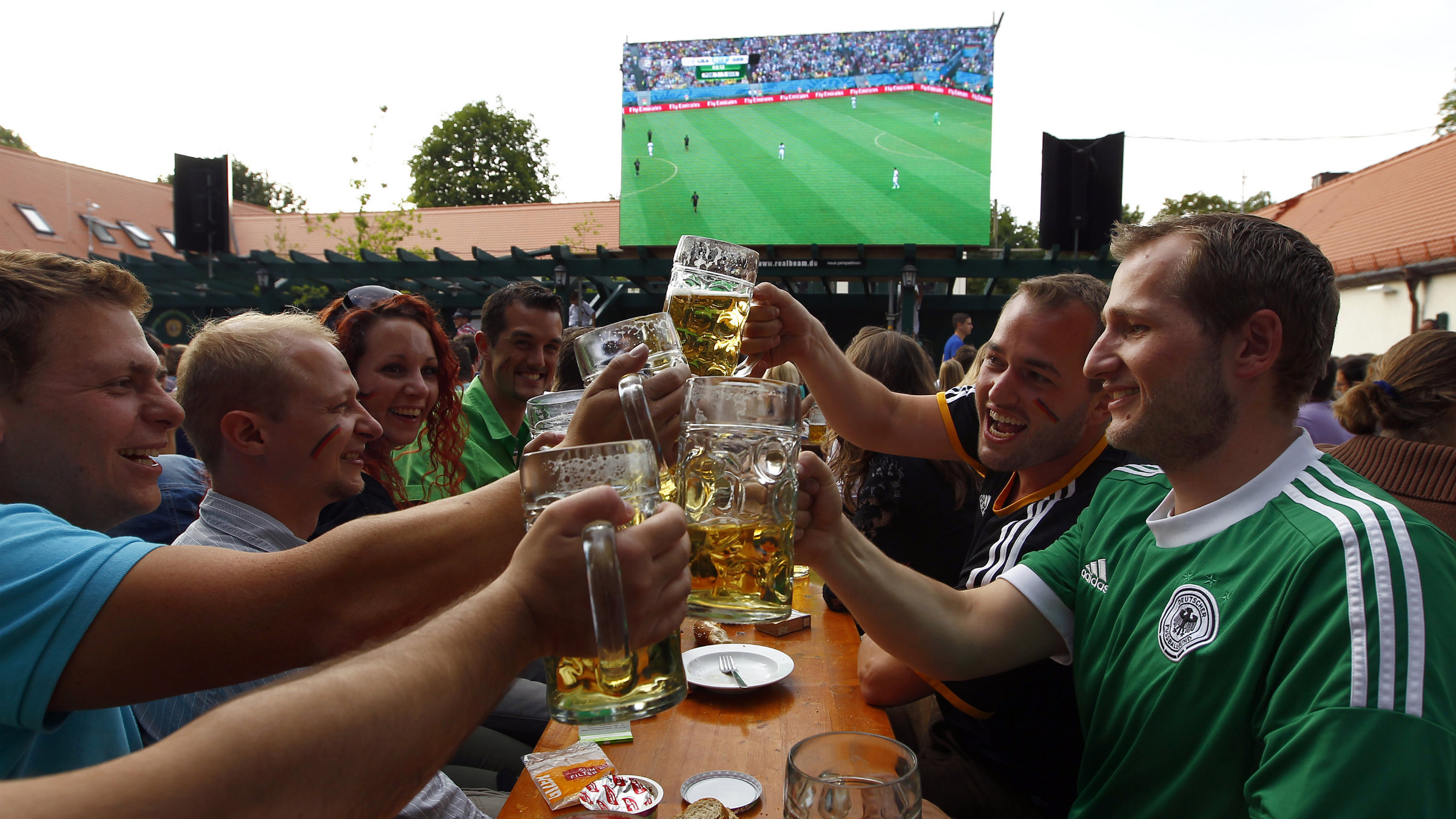 German soccer fans toast with beer as their team plays against the U.S. during their 2014 World Cup Group G soccer match, at public viewing in a beergarden 'Hirschgarten' in Munich June 26, 2014.